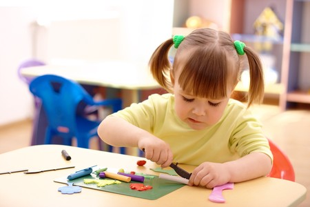 Cute little girl play with plasticine in preschool photo
