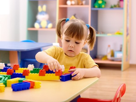 Cute little girl play with building bricks in preschool Stock Photo - 7119211