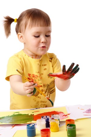 Cute cheerful child paint her fingers with colorful paints, isolated over white photo
