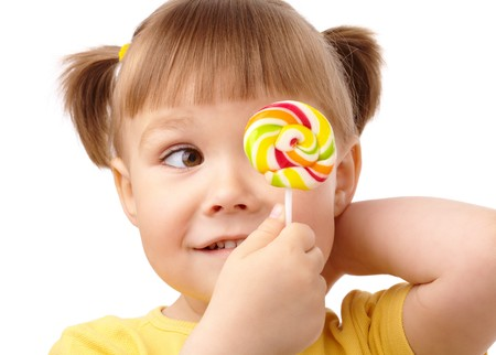 Cute little girl is looking at her colorful lollipop, isolated over white photo
