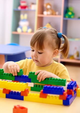 Cute little girl play with building bricks in preschool Stock Photo