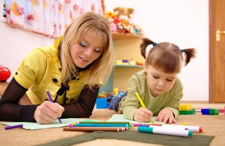 Juego de maestro con niño lindo en preescolar  Foto de archivo