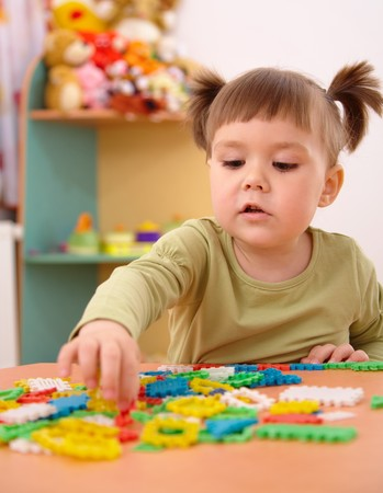 Cute little girl play with building bricks in preschool photo