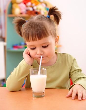 Gloomy little girl drinks milk in preschool photo