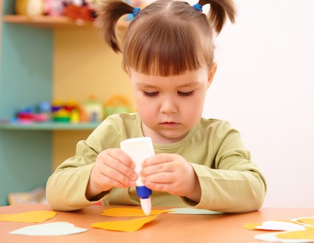 art activity: Cute little girl doing arts and crafts in preschool