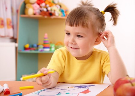 Cute little girl draw with felt-tip pen in preschool photo