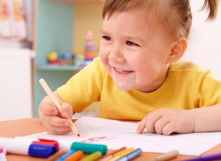 就学前のフェルトペンとかわいい女の子を描く