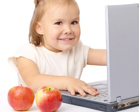 Cute happy girl with laptop and two apples, isolated over white photo