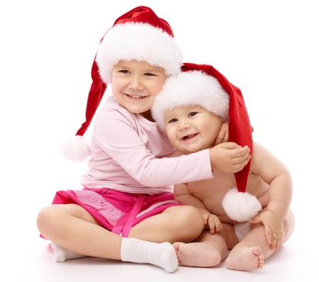 santa girl: Girl hugs her little brother, both wearing red Christmas caps and smile, isolated over white