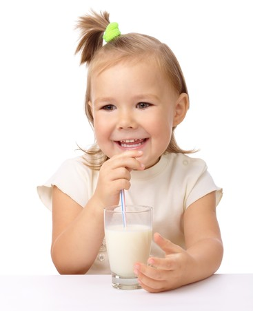 Cute little girl drinks milk using drinking straw, isolated over white photo