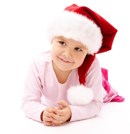 Adorable little girl, wearing red Christmas cap, isolated over white photo