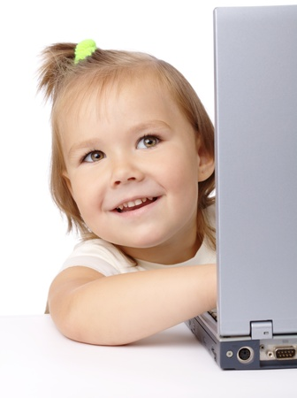 Cute little girl is looking out from her laptop, isolated over white photo