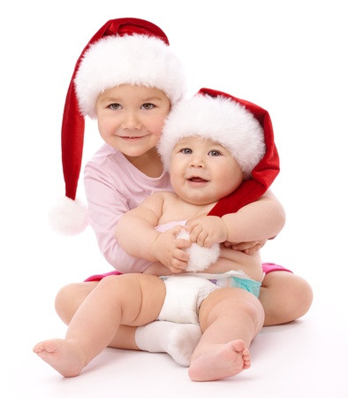 Girl hugs her little brother, both wearing red Christmas caps and smile, isolated over white photo