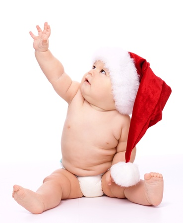 Adorable child with red Christmas cap is sitting on floor, raising his arm up, isolated over white photo