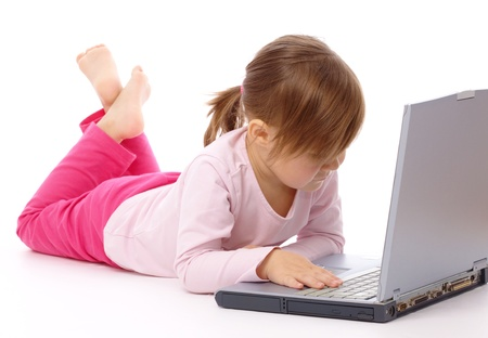 Cute little girl is laying on floor with her laptop,  isolated over white photo