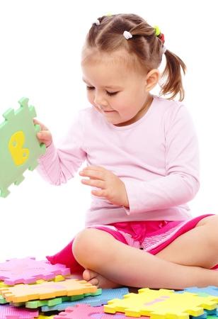 Niña bonita está jugando con el alfabeto mientras estaba sentado en el suelo, aislado en blanco Foto de archivo - 8418547