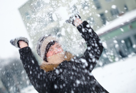 defending: Young girl is defending herself playing snowball fight