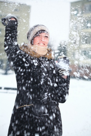 Young girl is defending herself playing snowball fight photo