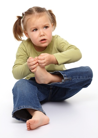 Little girl hurt her tiptoe, feeling pain, isolated over white photo
