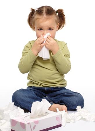 ragazza malata: Bambina soffia il suo naso mentre seduta sul pavimento, isolato over white