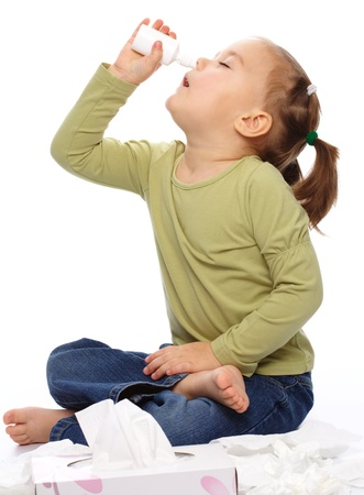 Little girl spraying her nose with nasal spray while sitting on floor, isolated over white photo