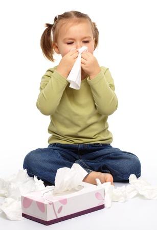estornudo: Ni�a sopla su nariz mientras estaba sentado en el piso, aislado en blanco