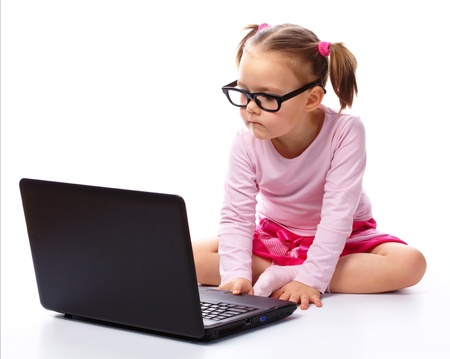 Cute little girl is sitting on floor with her laptop, wearing glasses, isolated over white photo