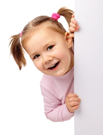 굽힘: Cute little girl is laughing while bending over blank board, isolated on white