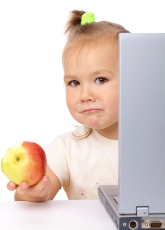 Cute little girl with laptop and red apple, isolated over white photo