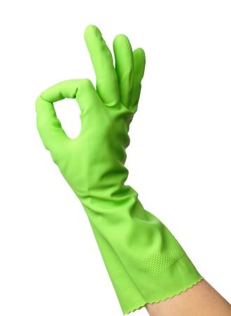 Mano usando guantes de goma verde muestra signo OK, aislado en blanco