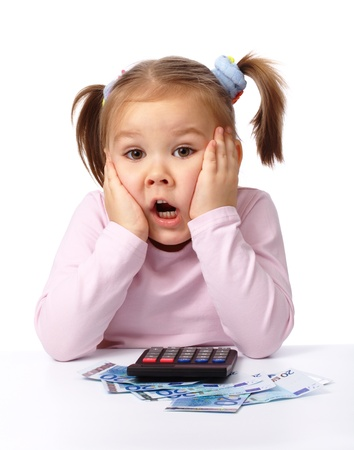 deadline: Cute little girl plays with money, holding her face in shock, isolated over white