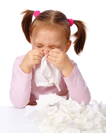cough medicine: Little girl blows her nose in paper tissue, isolated over white