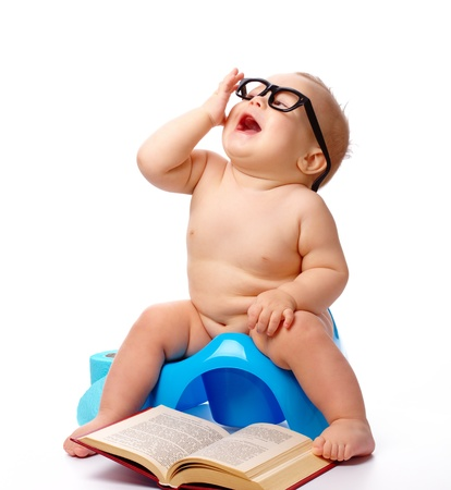 Child on potty play with glasses and book, isolated over white photo