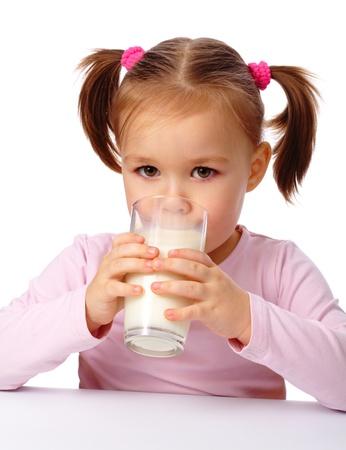 Cute little girl drinks milk, isolated over white photo