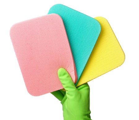 Few colorful washing sponges in hand wearing yellow glove, isolated over white photo