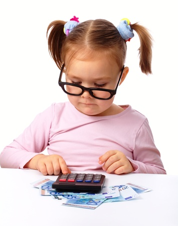 calculator money: Cute little girl plays with money, isolated over white