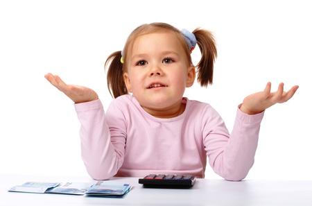 Schattig klein meisje met weinig twintig euro bankbiljetten en calculator schouderophalend haar schouders, geïsoleerd over white Stockfoto