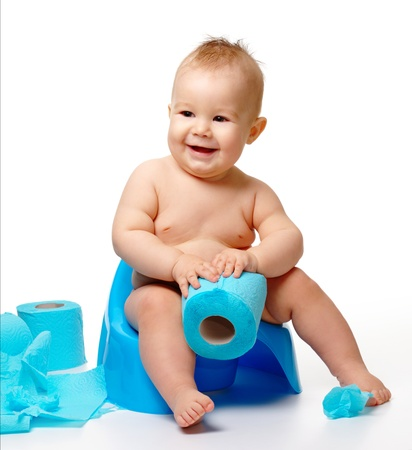 Child on potty play with toilet paper, isolated over white photo