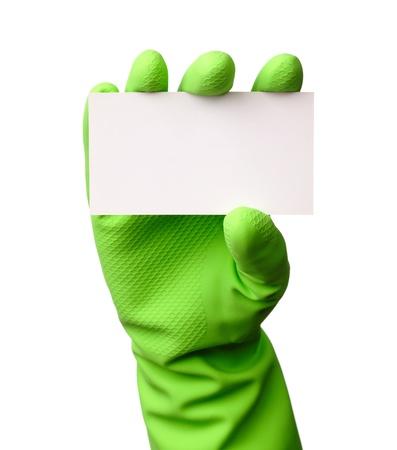 servicio domestico: Mano en guantes de goma verde mostrando la tarjeta de presentaci?n en blanco, aislado en blanco