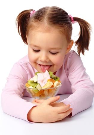 Cute little girl licks fruit salad, isolated over white photo