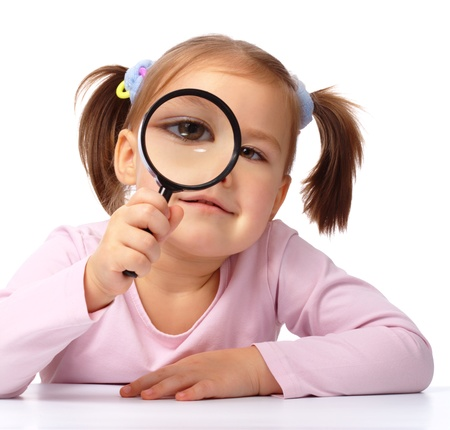 magnify: Curious little girl is looking through magnifying glass, isolated over white