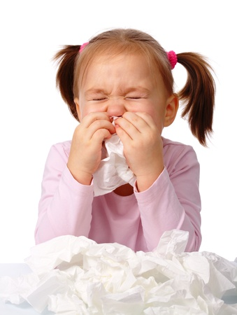 Little girl blows her nose, isolated over white photo