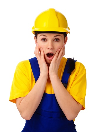 Young attractive construction girl holding her face in astonishment, isolated over white photo