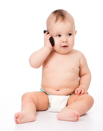 children talking: Cute little baby is talking on cell phone, isolated over white