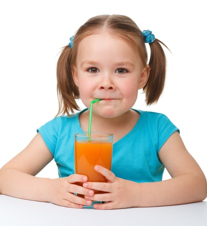 Cute little girl drinks orange juice using drinking straw, isolated over white photo