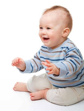 Happy child is sitting on floor, isolated over white photo