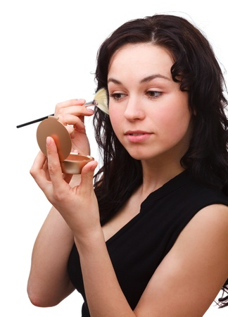 Young attractive girl is applying rouge using brush while looking at mirror, isolated over white photo