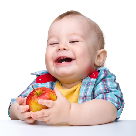 Cute little child is eating red apple and smile while sitting at table, isolated over white photo