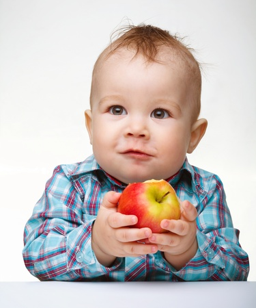 Cute little child is eating red apple while sitting at table, isolated over white photo
