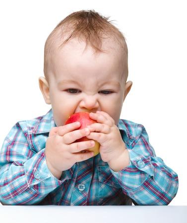 Ni�o lindo es comer manzana roja mientras estaba sentado a la mesa, aislada en blanco Foto de archivo - 9395803
